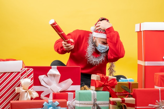 Front view young male sitting around presents blowing firecracker on yellow background
