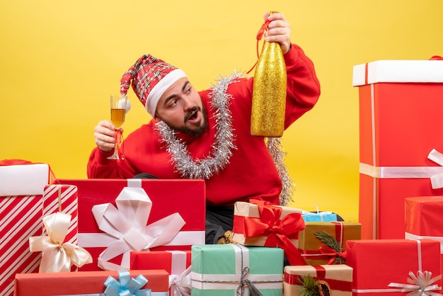 노란색 배경에 샴페인 축하 선물 주위에 앉아 전면보기 젊은 남성