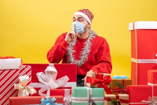 노란색 배경에 마스크에 선물 주위에 앉아 전면보기 젊은 남성