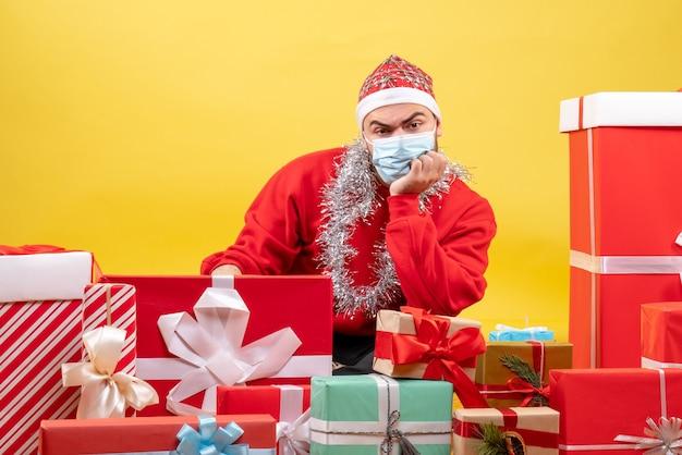 黄色の背景にマスクでプレゼントの周りに座っている正面図若い男性