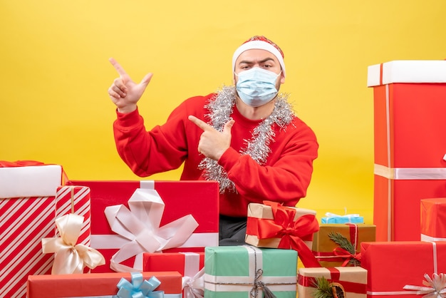 黄色のマスクでプレゼントの周りに座っている正面図若い男性