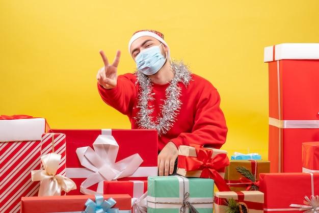 黄色の背景に滅菌マスクでプレゼントの周りに座っている若い男性の正面図