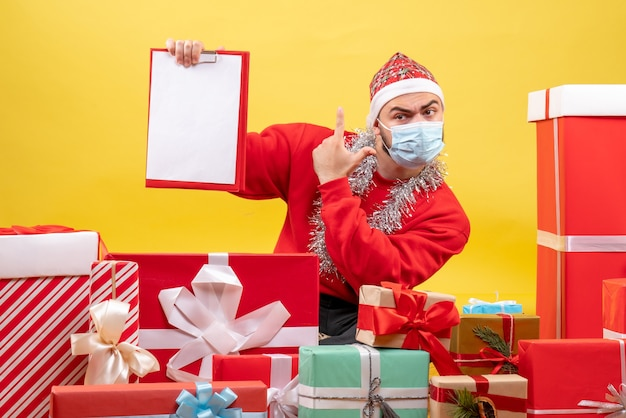 Front view young male sitting around presents in mask with note on yellow background