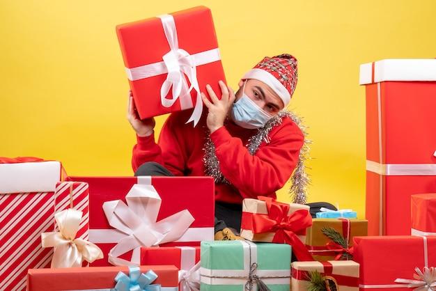 Вид спереди молодой самец сидит вокруг подарков на желтом фоне
