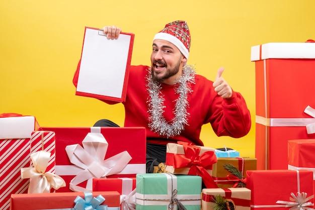 黄色の背景にプレゼントの周りに座っている正面図若い男性