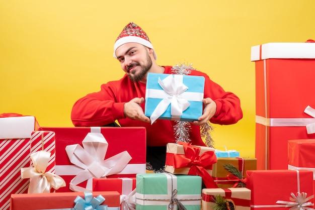노란색 배경에 선물 주위에 앉아 전면보기 젊은 남성