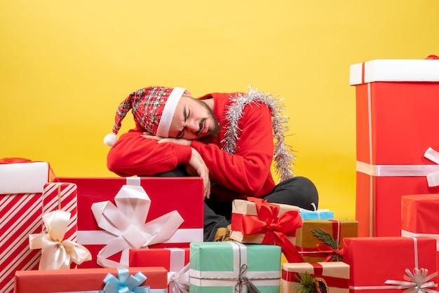 노란색 배경에 자 선물 주위에 앉아 전면보기 젊은 남성