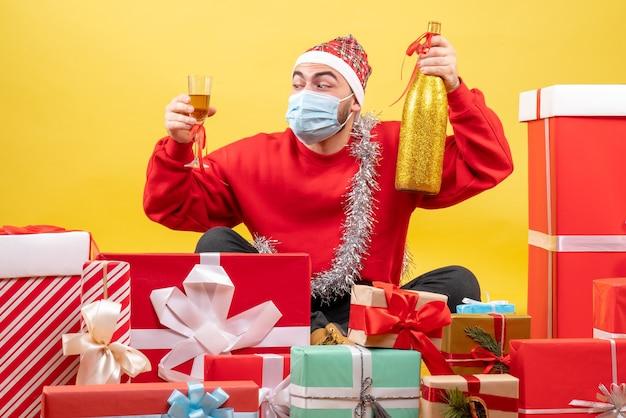 Вид спереди молодого мужчины, сидящего вокруг подарков с шампанским на желтом фоне