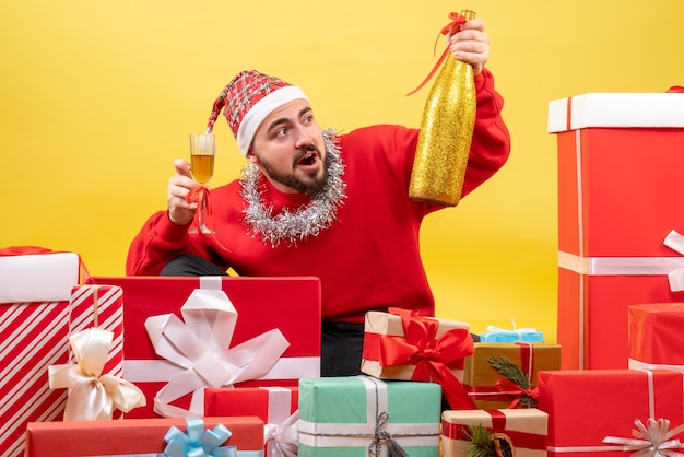 노란색 배경에 샴페인 선물 주위에 앉아 전면보기 젊은 남성