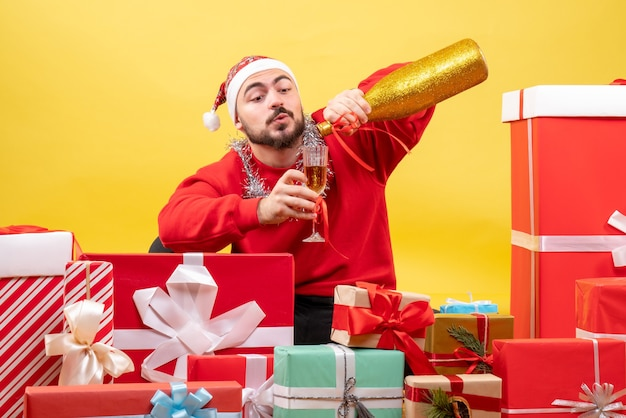 Front view young male sitting around presents with champagne on the yellow background