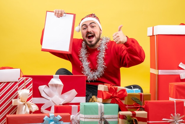Front view young male sitting around presents with note on yellow background