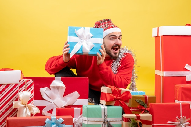 Front view young male sitting around presents on a yellow background