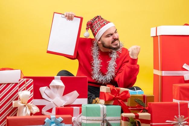 Giovane maschio di vista frontale che si siede intorno ai regali su priorità bassa gialla