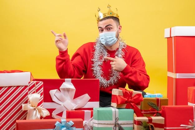 正面図黄色の背景の上のマスクでクリスマスプレゼントの周りに座っている若い男性