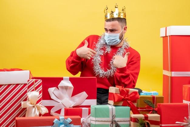 Вид спереди молодой самец, сидящий вокруг рождественских подарков в маске на желтом фоне