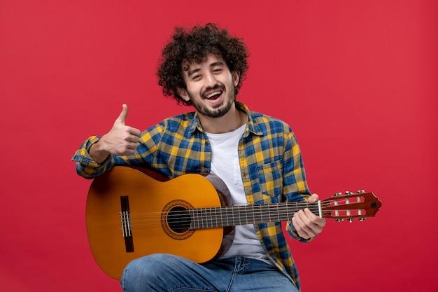 Vista frontale giovane maschio seduto e suonare la chitarra sulla parete rossa concerto musica banda colore suonare musicista applauso