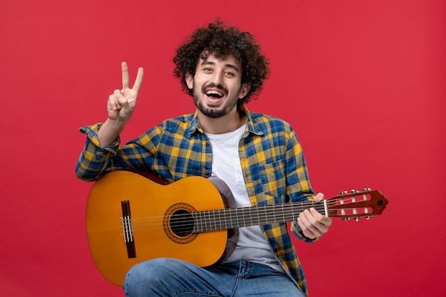 Vista frontale giovane maschio seduto e suonare la chitarra sul muro rosso musica dal vivo della banda di colori suona l'applauso del musicista