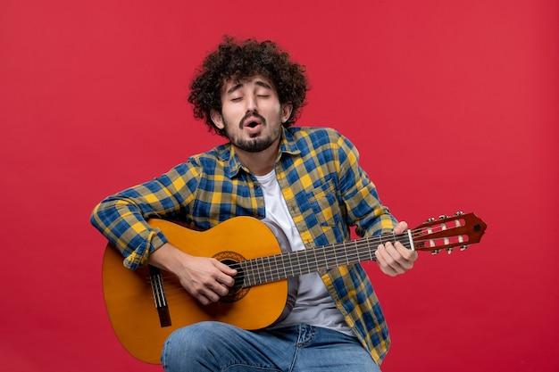Vista frontale giovane maschio seduto e suonare la chitarra sul muro rosso concerto dal vivo musicista applauso band suonare musica