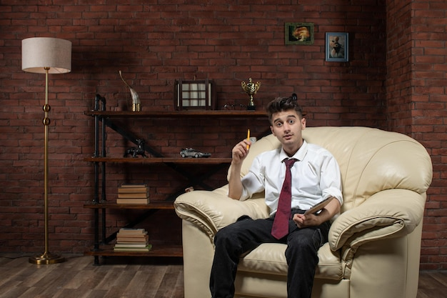 Vista frontale del giovane maschio seduto sul divano a scrivere note all'interno della stanza ufficio lavoro studente lavoro