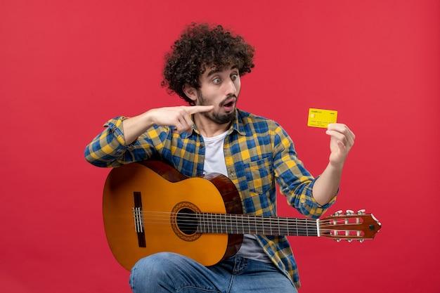赤い壁に銀行カードを持ってギターを持って座っている正面図若い男性音楽コンサート拍手ミュージシャンカラーライブ