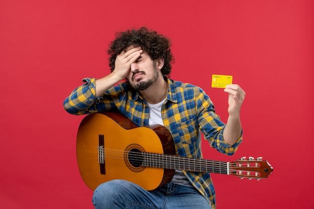Vista frontale giovane maschio seduto con la chitarra in possesso di carta di credito sul muro rosso performance concerto applausi musica dal vivo