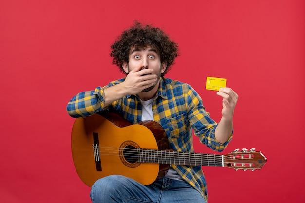 Vista frontale giovane maschio seduto con la chitarra che tiene la carta di credito sulla parete rossa musica concerto applauso musicista colori vendita live