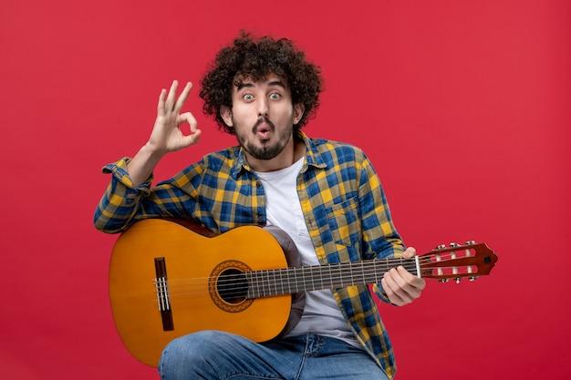 빨간 벽 콘서트 라이브 컬러 밴드 음악 연주 음악가 박수에 기타와 함께 앉아 전면 보기 젊은 남성