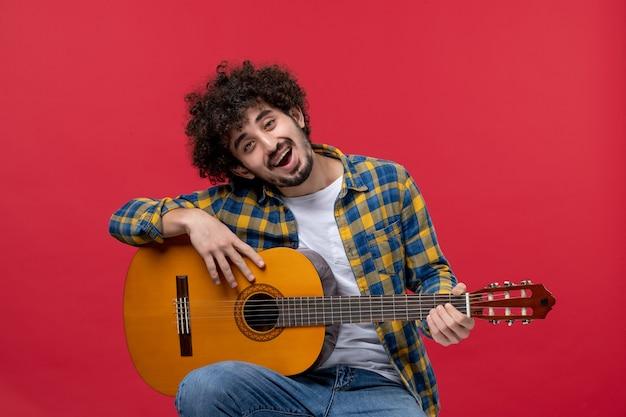 빨간 벽 콘서트 라이브 컬러 밴드 연주 음악가 박수에 기타와 함께 앉아 전면 보기 젊은 남성