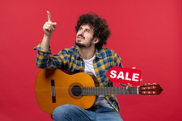 붉은 벽 콘서트 라이브 음악 컬러 박수 음악가 연주에 기타와 함께 앉아 전면 보기 젊은 남성