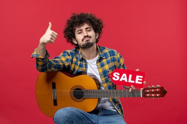 빨간 벽 콘서트 라이브 음악 박수 음악가 판매에 기타와 함께 앉아 전면 보기 젊은 남성