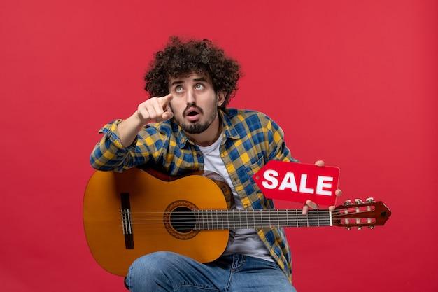 빨간 벽 콘서트 라이브 음악 색상 박수 판매 재생에 기타와 함께 앉아 전면 보기 젊은 남성