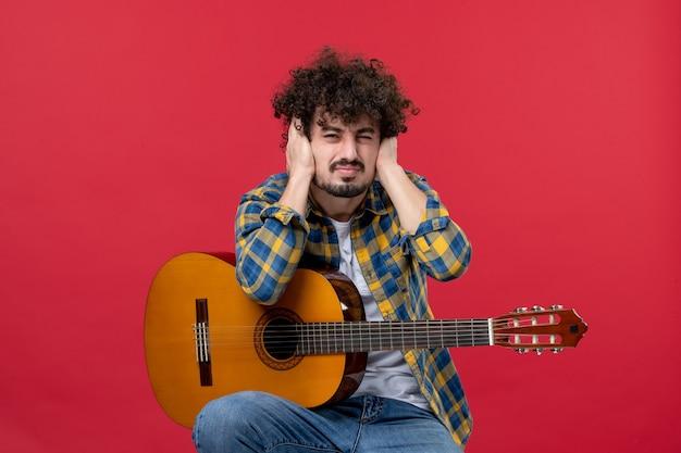 빨간 벽 콘서트 라이브 음악 음악가 박수 밴드에 기타와 함께 앉아 전면 보기 젊은 남성