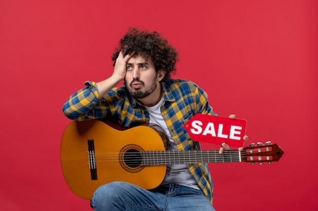 빨간 벽 콘서트 라이브 음악 컬러 음악가 판매 플레이에 기타와 함께 앉아 전면 보기 젊은 남성