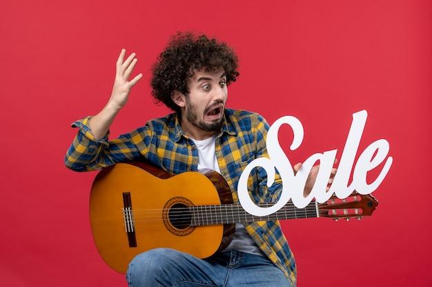 빨간 벽 콘서트 라이브 음악가 판매 재생 음악 색상에 기타와 함께 앉아 전면보기 젊은 남성