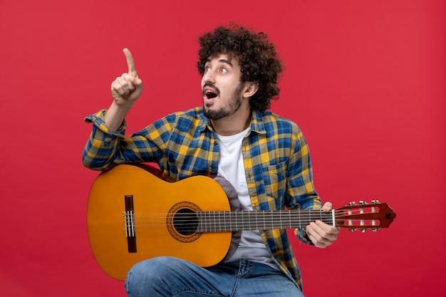 赤い壁にギターを持って座っている正面図若い男性はコンサートライブバンド音楽色ミュージシャンの拍手を再生します