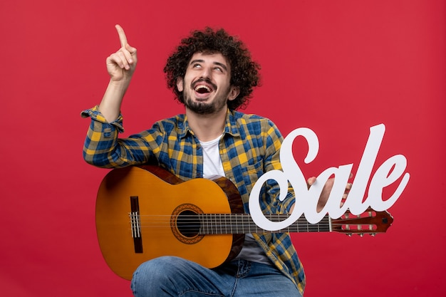 赤い壁にギターを持って座っている正面図若い男性演奏コンサートミュージシャンセール音楽色拍手ライブ