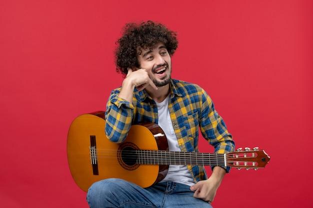 Vista frontale giovane maschio seduto con la chitarra sul muro rosso band concerto dal vivo musicista applauso suonare musica color