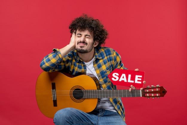 Vista frontale giovane maschio seduto con la chitarra sul muro rosso concerto colori dal vivo applausi musicista vendita suonare musica