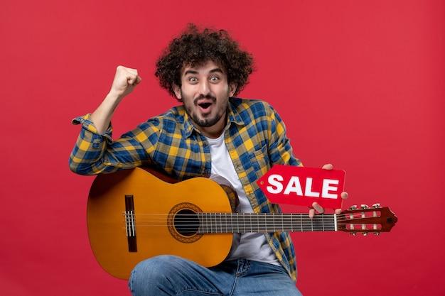 Vista frontale giovane maschio seduto con la chitarra sul muro rosso concerto musicista dal vivo suona musica applausi a colori