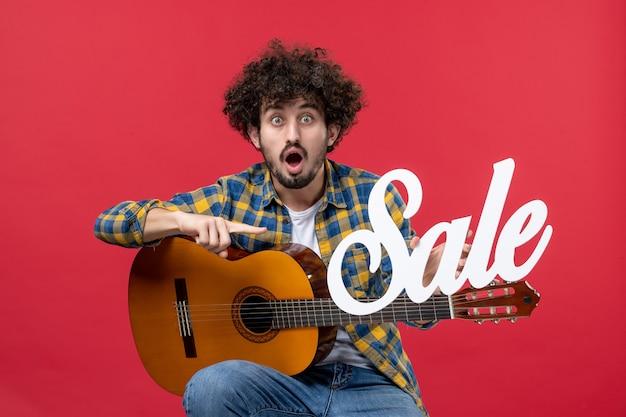 Vista frontale giovane maschio seduto con la chitarra sul muro rosso concerto musicista dal vivo vendita musica applausi a colori