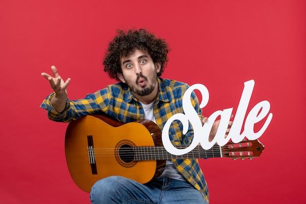 Vista frontale giovane maschio seduto con la chitarra sul muro rosso concerto vendita musicista dal vivo gioca applausi a colori