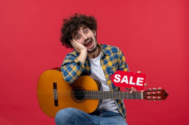 Vista frontale giovane maschio seduto con la chitarra sul muro rosso concerto vendita musicista dal vivo suona musica applausi a colori