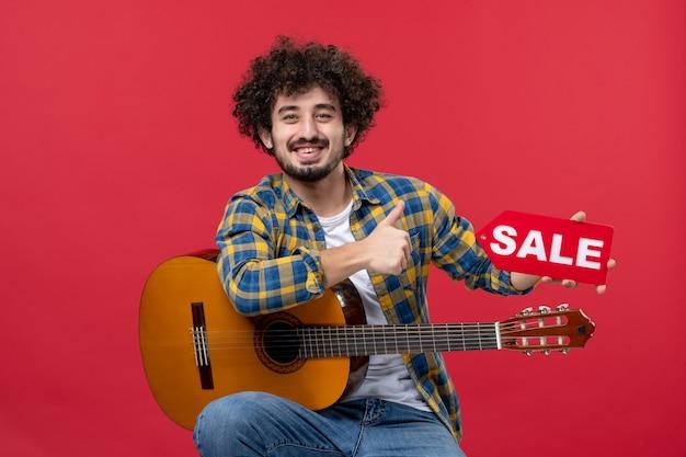 Vista frontale giovane maschio seduto con la chitarra sul muro rosso musica dal vivo applausi concerto vendita play
