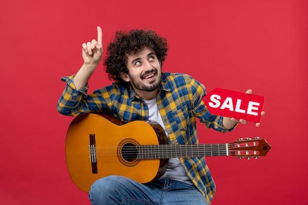 Vista frontale giovane maschio seduto con la chitarra sul muro rosso musica applausi concerto dal vivo vendita play