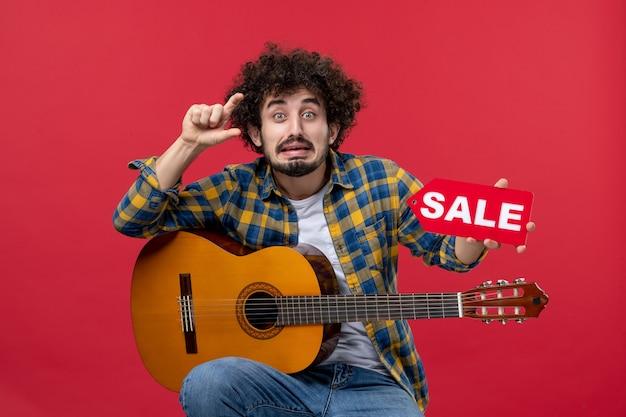 Vista frontale giovane maschio seduto con la chitarra sul muro rosso musica applausi dal vivo musicista concerto play