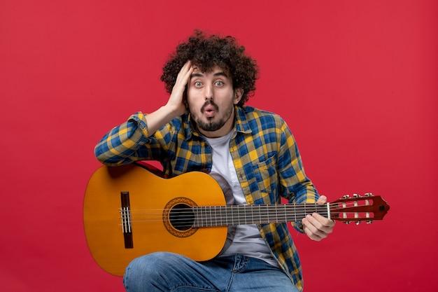 Vista frontale giovane maschio seduto con la chitarra sul muro rosso suona un concerto dal vivo musica applausi a colori
