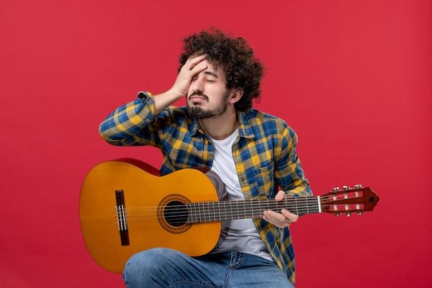 Vista frontale giovane maschio seduto con la chitarra sul muro rosso suona musica da concerto musicista colore applausi live band emozione