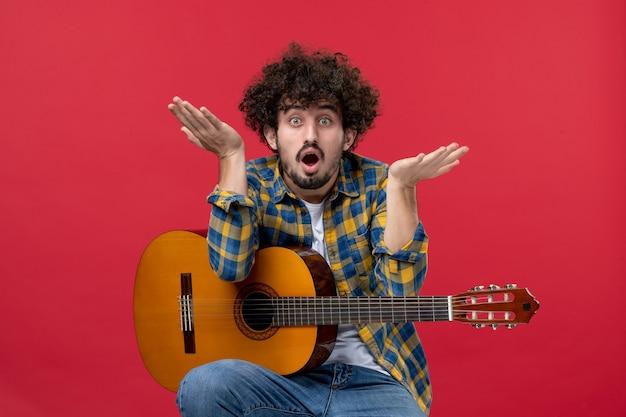 Vista frontale giovane maschio seduto con la chitarra sul muro rosso suona musica da concerto musicista colore applausi live band