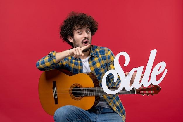 Vista frontale giovane maschio seduto con la chitarra sul muro rosso suona un concerto musicista vendita applausi a colori dal vivo