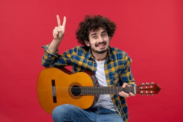 Vista frontale giovane maschio seduto con la chitarra sul muro rosso suona musica musicista applausi a colori concerto dal vivo